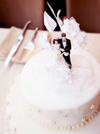 Tasty wedding cake, decorated with bride & groom design photo