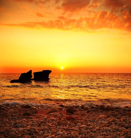 Beautiful warm sunset on the beach, seascape with calm ocean and rocks in the water Stock Photo - 9059337