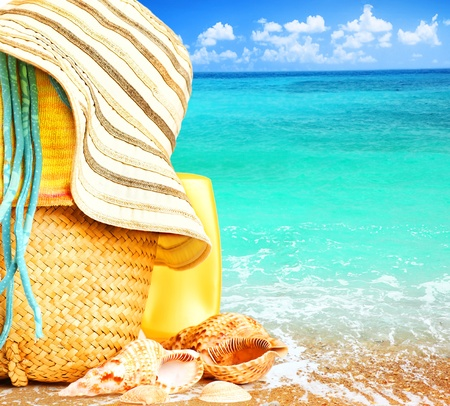 summer: Beach items over blue sea conceptual image of summertime vacation & holidays