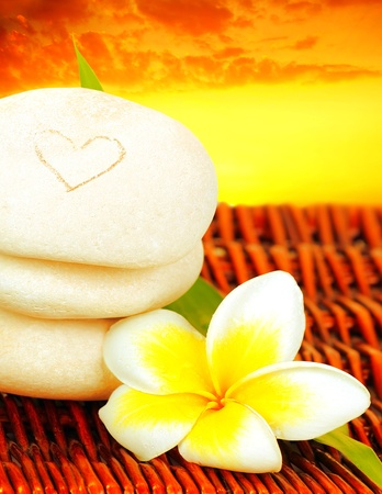 Spa stones in balance & frangipani flower over sunset, concept of vacation, relaxation, meditation & healthy balanced lifestyle photo