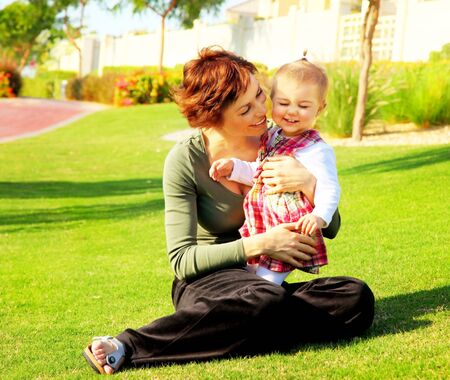 happy family concept: Mather & cute baby daughter playing outdoor in the park, happy family concept