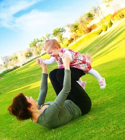 mamans: Mather & mignonne petite fille jouant en plein air dans le parc, le concept de famille heureuse
