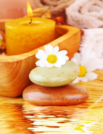 Spa candle and organic herbal soap with daisy flower, zen relaxation concept