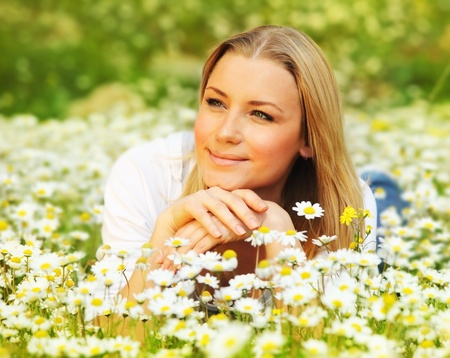 camomiles: Young beautiful girl laying on the daisy flowers field, outdoor portrait, summer fun concept