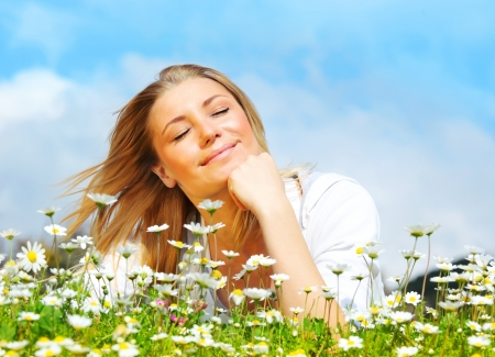 Young beautiful girl laying on the daisy flowers field, outdoor portrait, summer fun concept Stock Photo - 9179264