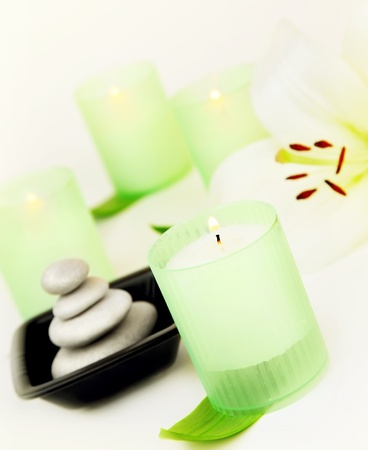 Candles and balanced zen spa stones with lily flower, relaxation vacation concept photo