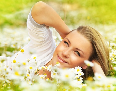 Young beautiful girl laying on the daisy flowers field, outdoor portrait, summer fun concept Stock Photo - 9327306