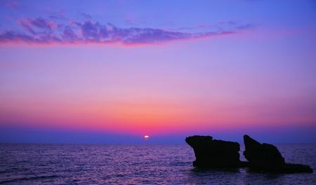 아름 다운 보라색 일몰 해변, 진정 바다와 푸른 물에 바위 경치