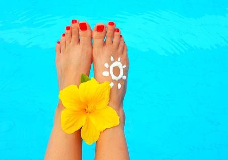 pies bonitos: Hermosas piernas femeninas con flores en la imagen conceptual de la piscina de vacaciones