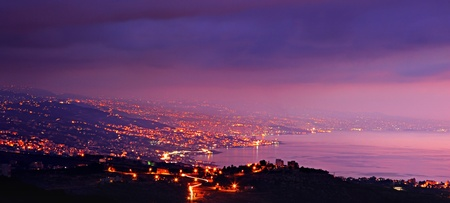 twilight: Panoramic mountains city at night with purple sky & sea