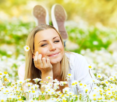 woman lying down: Young beautiful girl laying on the daisy flowers field, outdoor portrait, summer fun concept