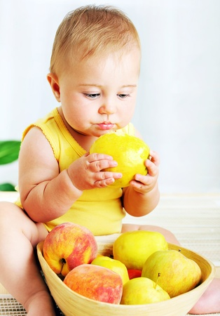 baby eating: Little baby eating apple, closeup portrait, concept of health care & healthy child nutrition