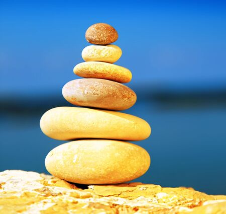 stacked stone: Zen spa balance stones, over blue calm sea background, conceptual image of relaxation & vacation Stock Photo