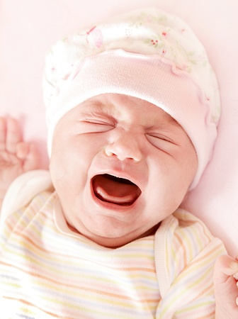 Closeup portrait of cute little baby girl crying in pink pajama & hat? photo