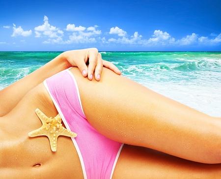 Bello cuerpo femenino en la playa, imagen conceptual de vacaciones, spa, viajes & verano vacaciones