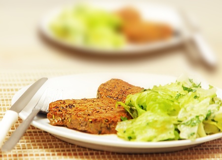 Delicious meat steak with green lettuce salad photo