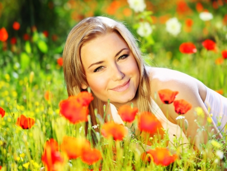 Young beautiful girl laying on the poppy flowers field, outdoor portrait, summer fun concept