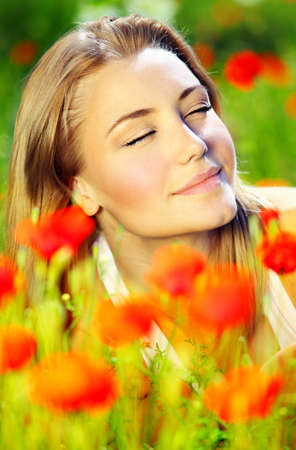 Young beautiful girl laying on the poppy flowers field, summer vacation & holidays concept Stock Photo - 9642291