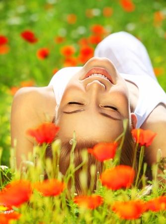 lying in grass: Hermosa joven de la amapola flores de vacaciones de verano, campo & concepto de vacaciones