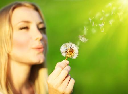 blowing dandelion: Felice bella ragazza che soffia il dente di Leone, su sfondo verde natura, messa a fuoco selettivo, concetto di desiderio