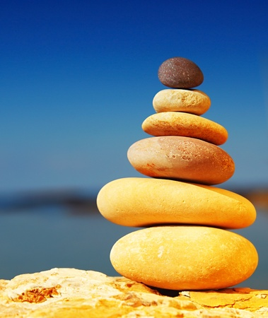 Zen spa balance stones, over blue calm sea background, conceptual image of relaxation & vacation photo