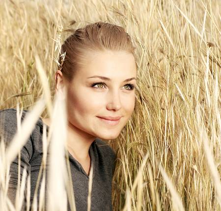 Young beautiful girl laying in the wheat field, outdoor portrait, summer fun concept photo
