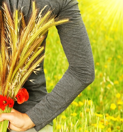 Wheat bouquet in girls hand, harvest concept photo