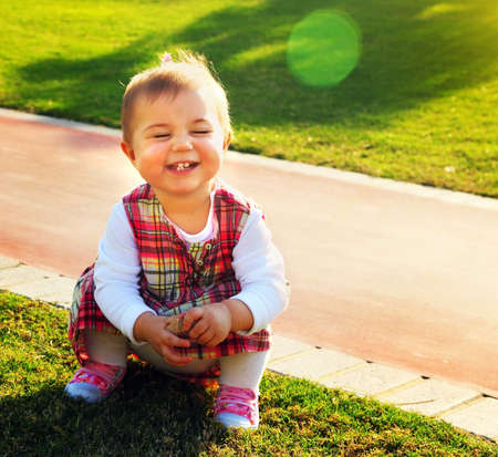 Sweet baby girl playing outdoor on the green grass photo