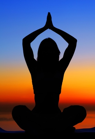 Healthy woman doing yoga outdoor, sunset over sea, body care & meditation concept photo