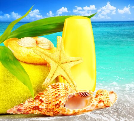 Beach items over blue sea conceptual image of summertime vacation & holidays photo