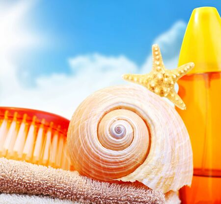Beach items over blue sky conceptual image of summertime vacation & holidays Stock Photo