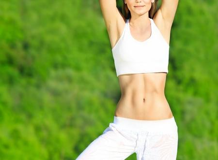skinny: Cuerpo de la mujer saludable deporte sobre fondo natural verde, concepto de atenci�n & fitness de cuerpo Foto de archivo
