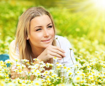 Young beautiful girl laying on the daisy flowers field, outdoor portrait, summer fun concept photo