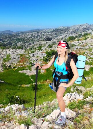 Traveling girl with backpack hiking in the mountains, eco tourism  photo