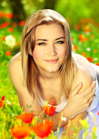Young beautiful girl enjoying on the poppy flowers field, outdoor portrait, summer fun concept Stock Photo