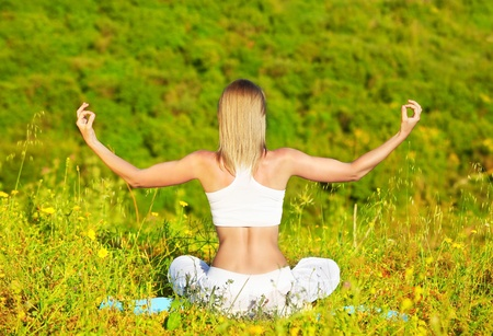 inner peace: Healthy female doing yoga outdoor, sitting in lotus posture, body care and inner peace concept Stock Photo