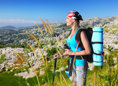trekking: Traveling girl with backpack hiking in the mountains, eco tourism, freedom concept