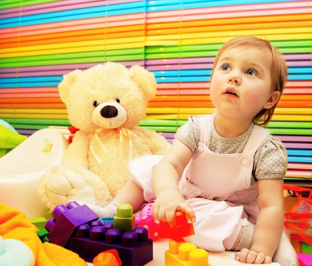 Little baby girl playing with colorful toy, child education concept photo