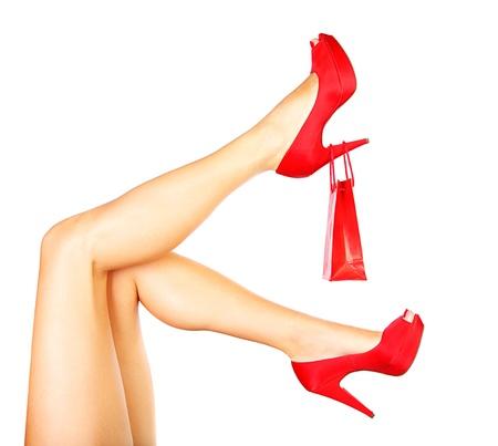 tacones: Hermosas piernas femeninas con tacones rojos y bolsa aisladas sobre fondo blanco, en concepto de gasto de dinero