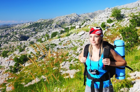 adventure holiday: Traveling girl with backpack hiking in the mountains, eco tourism
