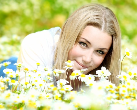 Young beautiful girl laying on the daisy flowers field, outdoor portrait, summer fun and freedom concept photo