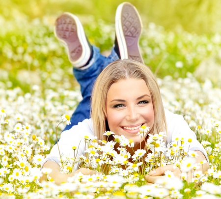 Cute happy girl enjoying daisy flower field, nature at summertime, leisure fun outdoor photo