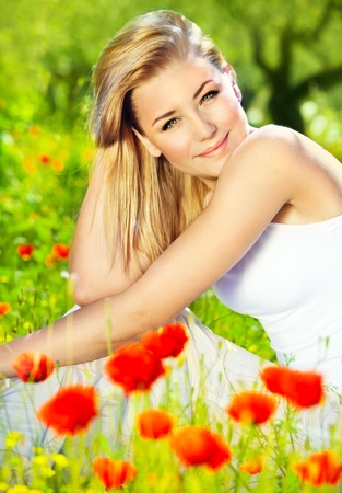 Lovely happy female closeup portrait, sitting in the poppy flower field, enjoying nature, summertime leisure concept photo