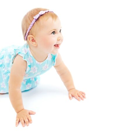 Adorable little baby girl laughing, crawling and playing at studio, isolated on white background photo