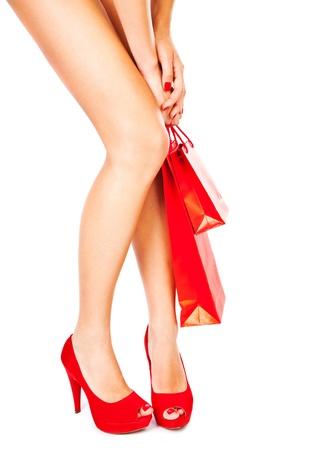 Schöne weibliche Beine mit roten High Heels halten Einkaufstüten auf weißem Hintergrund, Geldausgeben Konzept isoliert Standard-Bild