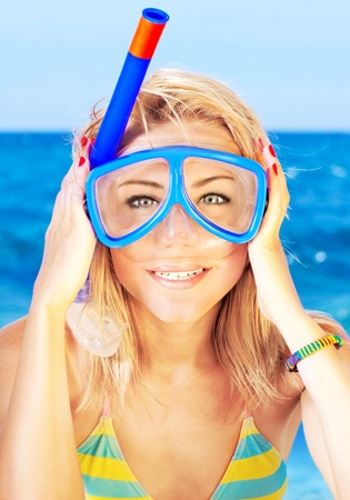 woman diving: Funny portrait of a beautiful young girl with an underwater mask on the beach, vacation and summertime outdoor fun concept