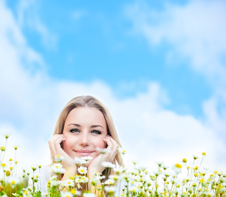 Happy young female lying on the flower field, over blue cloudy sky, with copyspace, leisure, fun and wellness concept photo