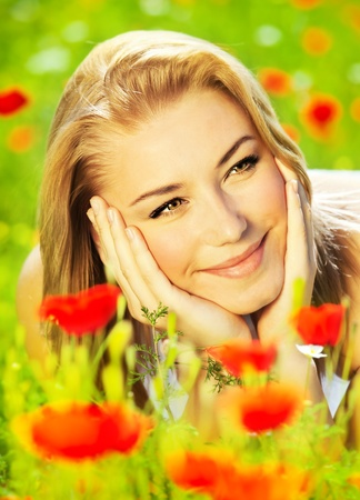 Lovely happy female closeup portrait, lying down in the poppy flower field, enjoying nature, summertime leisure concept photo