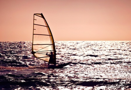 Windsurfer silhouette over sea sunset, panoramic beach landscape, summertime fun, sport, activities, vacation and travel concept photo