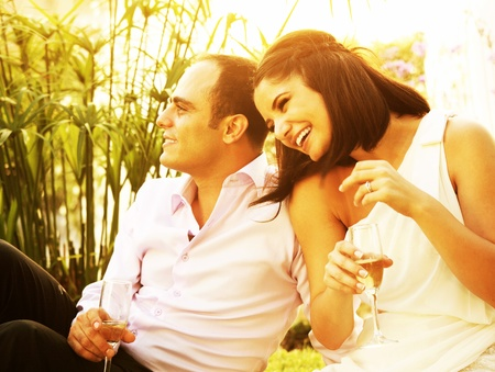Happy young couple drinking champagne outdoor, laughing and enjoying wedding day photo